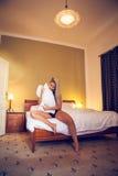 Verlockende junge Dame in der Liebe, die auf dem Bett und den Spielen mit einem Kissen sitzt Stockfoto