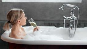 Verlockende junge Frau, die des Schaumbades Seitenansicht nehmend trinkendem Champagner sich entspannt stock footage