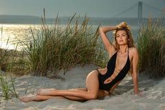 Verlockende junge Frau im sexy schwarzen Badeanzug, der auf den Sand am Strand legt Lizenzfreie Stockfotos