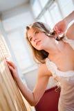 Verlockende junge hübsche Frau in den Pyjamas, die oben auf Balkon mit Fensterläden schauen, beleuchten auf Hintergrundporträt Stockfotografie