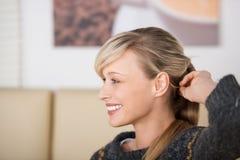 Verlockende lächelnde Frau, die mit ihrem Haar spielt Stockfotografie