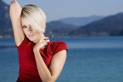 Verlockende schöne blonde Frau durch einen See Stockfoto
