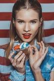 Verlockendes blondes Hippie-Mädchen in der amerikanischen patriotischen Ausstattung, die kleinen Kuchen mit uns Flagge auf Hinter Lizenzfreies Stockfoto
