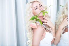Verlockendes blondes mit einer Rose in ihrem Mund Stockbild