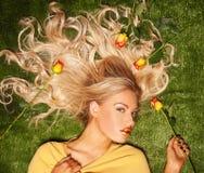 Verlockendes blondes mit ihrem Haar bedeckt in den Rosen Lizenzfreies Stockbild