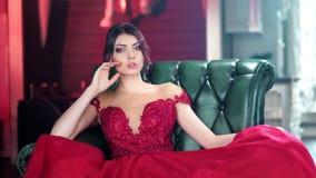 Verlockendes hispanisches junges Mädchen im roten Abendkleid des Zaubers, das auf mittlerem Schuss des Weinleselehnsessels sitzt stock video