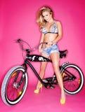 Verlockendes junges blondes auf einem Fahrrad Stockfotos