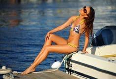 Verlockendes Modell, das stilvolle Badebekleidung und Sonnenbrille trägt und am Rand des Motorboots aufwirft Stockbild