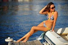Verlockendes Modell, das stilvolle Badebekleidung und Sonnenbrille trägt und am Rand des Motorboots aufwirft Stockfotografie