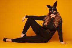 Verlockendes Plusgrößenmädchen in der Häschenmaske, die auf dem Boden aufwirft Stockfoto