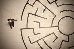 Verloren bedrijfsmens die een manier in cirkellabyrint zoeken Stock Foto's