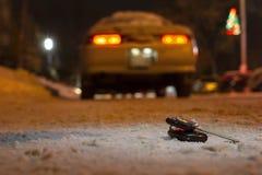 Verloren die autosleutels op de weg met de eerste sneeuw bij nacht wordt gepoederd Op vage achtergrond stock afbeeldingen