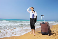 Verloren zakenman met zijn bagage die naar manier op een strand zoeken Stock Afbeelding