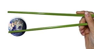 Verlorene blaue Planetenerde zwischen grünen Essstäbchen Stockfotos