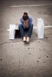 Verlorene Frau, die im Parkplatz mit Beuteln sitzt Lizenzfreie Stockfotografie