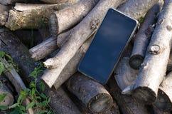 Verlorene Handyschwarzfarbe sitzt im Freien unter dem Stapel des Brennholzes lizenzfreies stockfoto