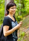 Verlorene smilling Frau in der Landschaft, die eine Karte hält Lizenzfreies Stockfoto