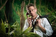 Verlorener Geschäftsmann, der einen Telefonanruf im Dschungel hat Stockfotos