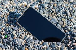 Verlorener Handy auf dem Strand unter den Seekleinen Kieseln stockbilder