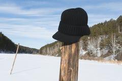 Verlorener Hut auf dem Pfosten auf dem Fluss in der Wintersaison Stockbilder