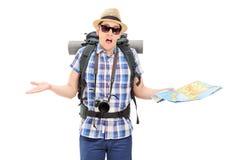 Verlorener männlicher Tourist, der eine Karte hält und mit den Händen gestikuliert Stockfotografie