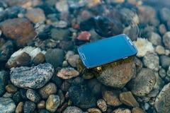 Verlorener Smartphone auf dem Wasser Stockbild