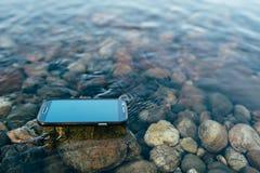 Verlorener Smartphone auf dem Wasser Stockbilder