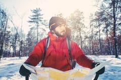 Verlorener Wanderer überprüft Karte am schneebedeckten Wald Stockbild