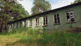 Verlorenes einstöckiges Haus mit großen Fenstern im Pinery, Kamera bewegt sich vorwärts auf Haus durch Gras stock video footage
