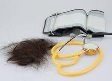 Verlorenes Haar gesetzt nahe Stethoskop und Sphygmomanometer stockfotos
