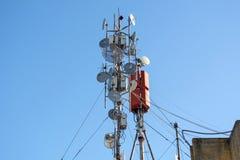 Verlost Antennen des drahtlosen Netzwerks, der Telekommunikation und der Satellitenschüsseln auf einem Gebäudedach Stockbild