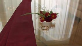 Verlovingsringen, band en boutonniere glaslijstbruidegom vóór de ceremonie stock footage