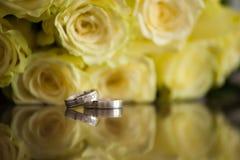 Verlovingsringen met gele rozen stock afbeeldingen