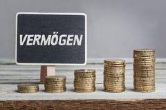 Vermögen estate in German language. Vermögen estate in German language, white chalk type on black board, Euro money coin stacks of growth on wood table Stock Photos