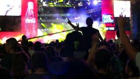 Vermaak van grote menigte van mensen, Overleg, dansmuziek in prestaties, heldere flitsen van kleur op stadium, stadium stock videobeelden