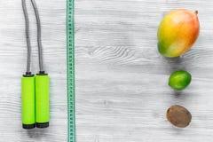 Vermageringsdieetdieet Vruchten mango, kalk, kiwi en touwtjespringen op de grijze houten mening van de lijstbovenkant copyspace royalty-vrije stock foto's