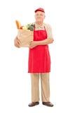Vermarkten Sie den Verkäufer, der eine Tasche voll von den Lebensmittelgeschäften hält Lizenzfreies Stockbild