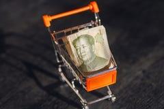 Vermarkten Sie Warenkorb mit einer Banknote des Chinesen Yuan und Gesicht des Führers Mao, als Symbol der modernen internationale Stockfotos