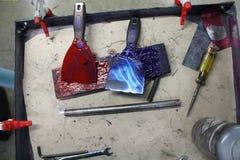 Vermelho azul dos raspadores da tinta da pintura das ferramentas na bandeja imagens de stock royalty free