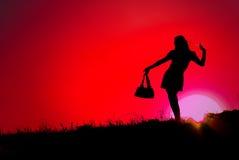 Vermelho bonito da mulher e do por do sol Imagem de Stock