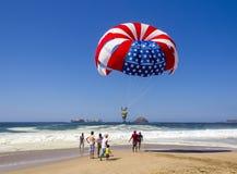 Vermelho, branco e azul do parasail da bandeira americana contra o céu azul brilhante Fotografia de Stock