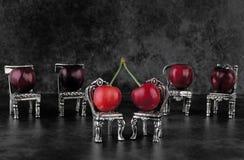 Vermelho - cerejas maduras deliciosas em cadeiras e na parte traseira de prata pequenas da obscuridade Imagem de Stock Royalty Free
