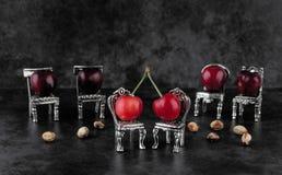 Vermelho - cerejas maduras deliciosas nas cadeiras de prata com cherrystones o Foto de Stock