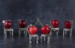 Vermelho - cerejas maduras deliciosas nas cadeiras de prata e no fundo escuro Imagem de Stock