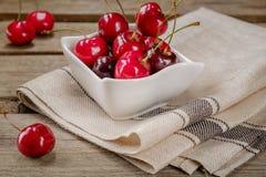 Vermelho de cereja em uma bacia de madeira Foto de Stock