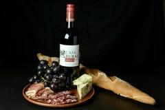 Vermelho de vinho espanhol, uvas, queijo azul, prosciutto cortado e baguette do francês do salame Imagens de Stock Royalty Free