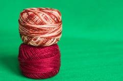 Vermelho e bolas do fio de mescla de um fio em um fundo verde Foto de Stock Royalty Free