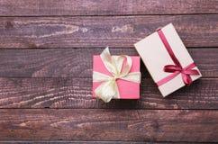 Vermelho e caixa de presente do ouro no fundo de madeira Fotografia de Stock Royalty Free