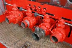 Vermelho e prata dos torneiras da mangueira do carro de bombeiros do bombeiro em seguido imagens de stock