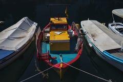 Vermelho ensolarado, turquesa e barco de pesca mediterrâneo amarelo na água em Euboea - Nea Artaki, Grécia Foto de Stock